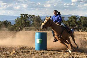Connie Wyatt running the barrels on her horse.